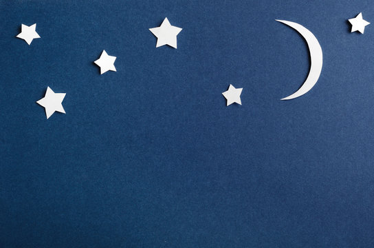 Moon and stars on blue background top view. Night sky objects with shadow close up. Decorative backdrop. Childish applique, homemade postcard. Starry heaven. Kid bedtime, nighttime concept.