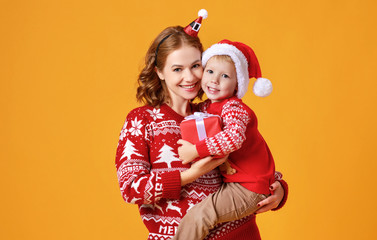 happy family mother and child son with christmas gifts on yellow background
