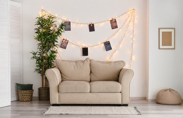 Interior of room with sofa and glowing garland with photos on white wall