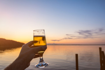Having a fresh cold beer at the seashore during a beautiful colorful sunset