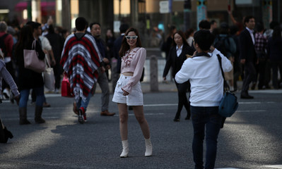 A woman poses for a photo on Shibuya Crossing, known as the world's busiest pedestrian crossing, Shibuya, Tokyo
