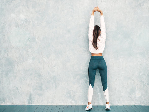 Back view of fitness woman in sports clothing looking confident.Young female wearing sportswear. Beautiful model with perfect tanned body.Female stretching out before training near gray wall in studio