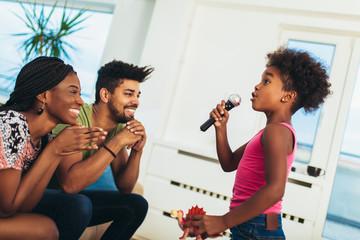 African american family enjoy singing karaoke at home, having fun. Fotobehang