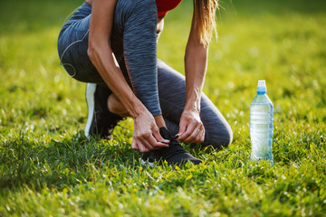 Cropped picture of caucasian woman in sportswear kneeling on meadow and tying shoelace on sneaker. Next to her is bottle of water. Sunny morning in nature.