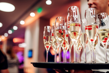 Cropped picture of waiter holding glasses of champagne on tray. Bar interior.