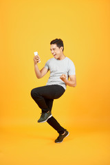 Cheerful young Asian man dressed in t-shirt jumping over orange background make winner gesture.