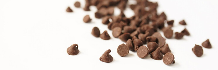 Semi Sweet Chocolate Chips isolated banner on white background close up. Selective focus.Top view. Copy space