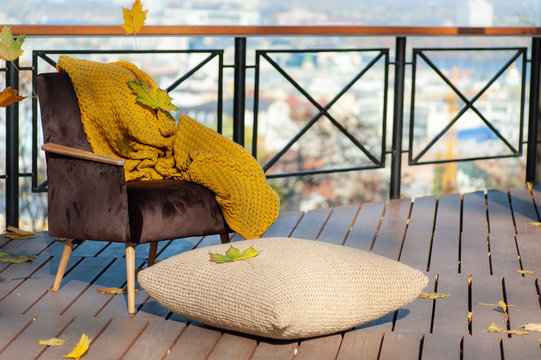 old brown chair, yellow blanket and jute flooring pillow on autumn terrace with beautiful blurred city view