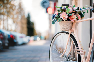 Foto op Canvas Fiets White bicycle with basket of flowers standing near the door on the street in city.
