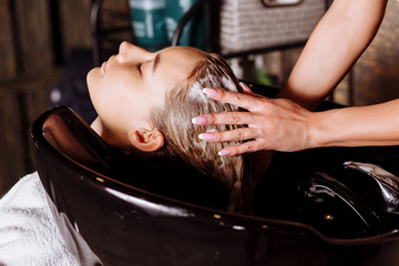Beautiful woman washing hair in a hair salon