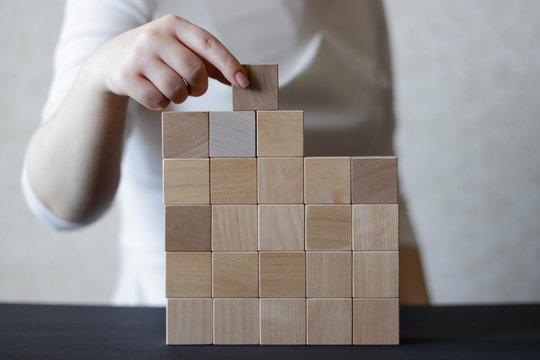 Woman's hand stacking wooden blocks. Business development concept.