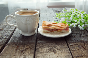 Apple pie and cup of coffee with flowers on table