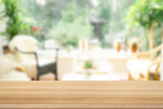 Brown empty wooden table top with blurred living room that can see garden background. Light wood with blurry in living room interior.