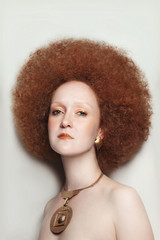 Vintage style portrait of young beautiful woman with fancy makeup and afro hair
