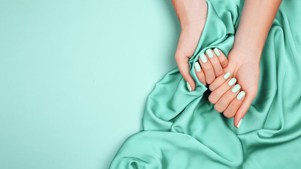 Fotobehang Manicure Hands of a young girl on a mint silk cloth, manicure on a trendy background , green polish