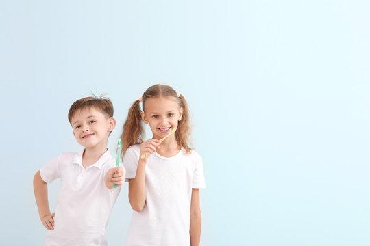 Portrait of little children brushing teeth on light background