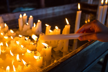 Hand lighting a candle in the church