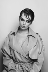 Vintage style black and white portrait of young beautiful woman in leather coat