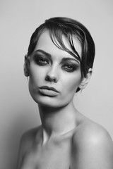 Vintage style black and white portrait of young beautiful woman with smoky eye makeup
