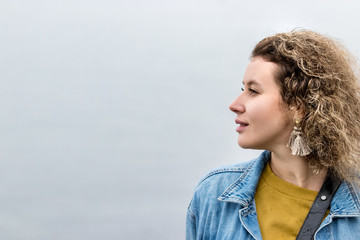Portrait of a young woman with curly hair looking away dreaming, outdoors, profile view.