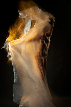 Body of a beautiful girl gracefully fits a cellophane film fluttering in the wind. In defocusing, it is illuminated with a fiery yellow color. Artistic, conceptual, avant-garde photography.