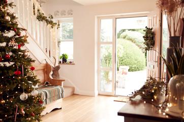 Hallway Of Home Decorated For Christmas Viewed Towards Open Front Door