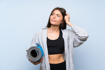 Young sport girl with mat over isolated blue background having doubts and with confuse face expression
