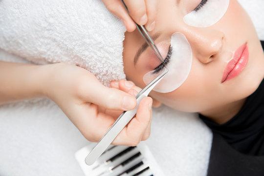 Eyelash extension procedure. Master tweezers fake long lashes beautiful female eyes