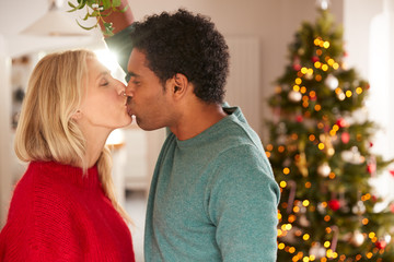 Loving Couple Kissing Under Mistletoe In House Decorated For Christmas