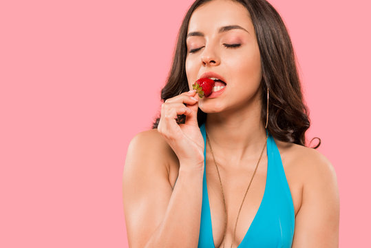 sexy woman eating tasty strawberry isolated on pink