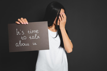 Young woman holding card with words IT'S TIME TO TALK ABOUT IT against dark background. Space for text