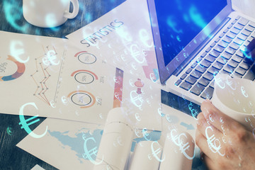 Double exposure of businessman's hands with laptop and stock market graph background. Concept of...