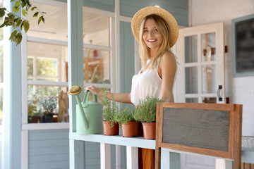 Young woman with watering can and home plants on veranda, space for text