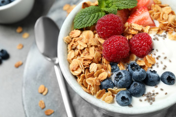 Foto op Plexiglas Kruidenierswinkel Tasty homemade granola with yogurt and berries on grey table, closeup. Healthy breakfast