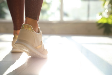 Young woman wearing stylish sneakers indoors, closeup