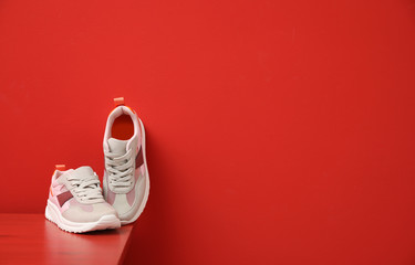 Stylish women's sneakers on wooden table near red wall, space for text