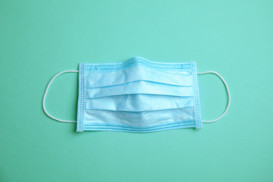 Medical face mask on turquoise background, top view