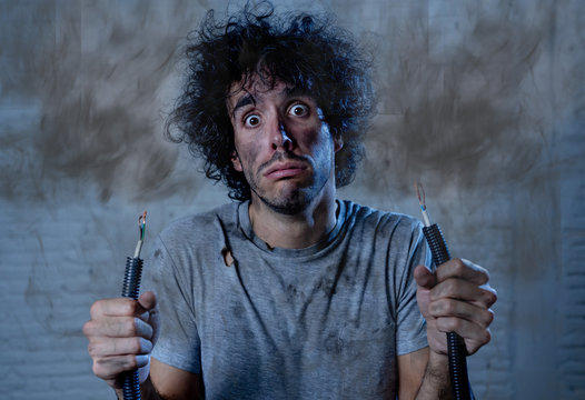 Funny image of man holding electrical cable after getting electric shock