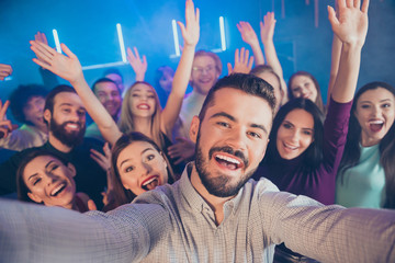 Close-up photo portrait of large crowd cheerful wit toothy beaming smile bearded youth youngster in fog smoke neon lights celebrating birthday taking selfie