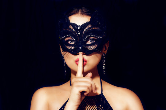 The girl in the mask. Masquerade, halloween. Girl in a cat mask. Beautiful woman shows a sign of silence