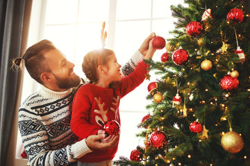 happy family father and child girl decorated Christmas tree