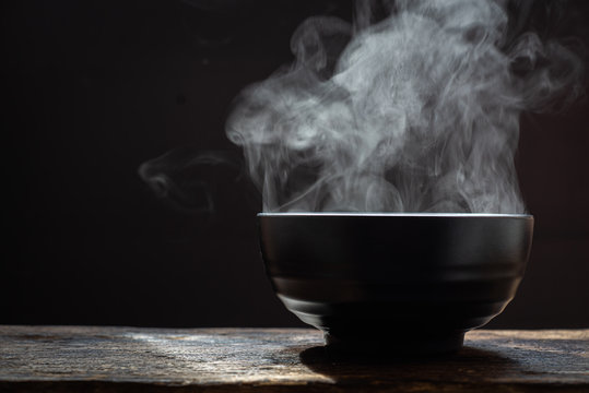 Hot food concept.Bowl of hot soup. steam of hot soup with smoke wood bowl on dark background.selective focus