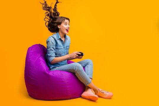 Portrait of her she nice attractive cheerful crazy addicted girlish wavy-haired girl sitting on bag chair playing game air blows hair isolated on bright vivid shine vibrant yellow color background