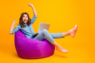 Fototapete - Portrait of her she nice attractive lovely cheerful cheery wavy-haired girl sitting on bag chair celebrating e-commerce breakthrough isolated on bright vivid shine vibrant yellow color background