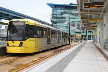 MANCHESTER, UK - APRIL 22, 2013: People board Metrolink tram in Manchester, UK. Manchester Metrolink serves 21 million rides annually (2011).