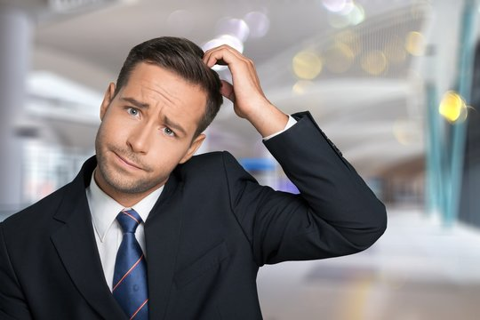 Young businessman scratching his head, hard decision