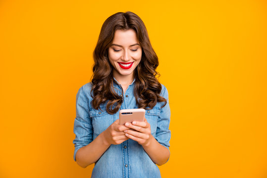 Photo of cheerful cute girl looking for new information through social media smiling toothily holding telephone isolated over yellow vivid blue background