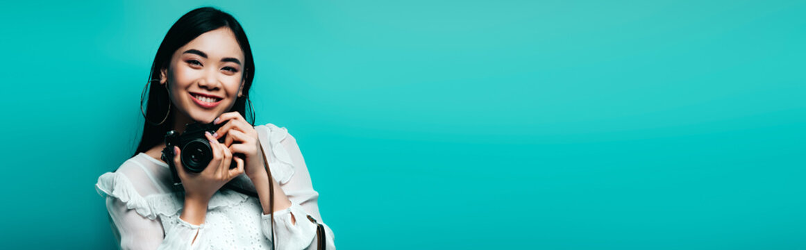 happy asian woman in white blouse holding digital camera on blue background, panoramic shot