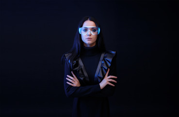 Wall Mural - Beautiful woman in glasses of virtual reality on dark background. Augmented reality, future technology concept. VR. Futuristic 3d glasses with virtual projection. Blue neon light.