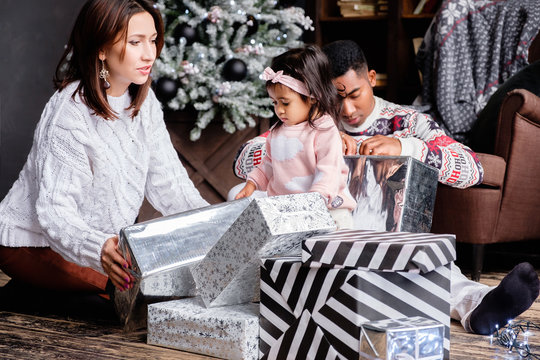 Mixed race Asian Mom family African American dad open boxes with Christmas gifts on background of Christmas tree decorated with black balls. Concept of festive mood and family holiday